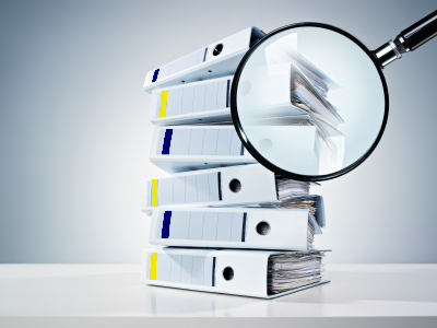 a pile of examining documents with a magnifying glass